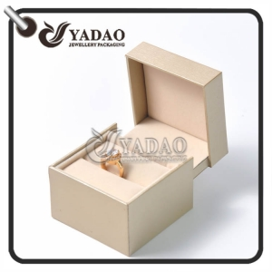 Luxurious unique customized plastic ring box covered with golden pu paper with nice soft velvet.